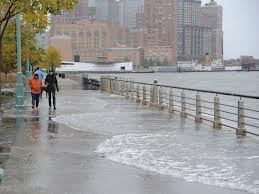 image showing hudson river storm surge flood waters covering most of the surface of a riverfront walkway, with two pedestrians dressed in rain gear walking towards the camera.