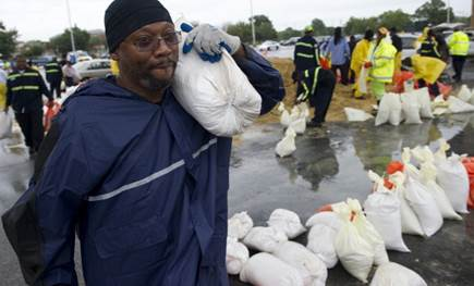 Man standing in the rain wearing a raincoat, with a sandbag on his shoulder. Around him are more sandbags.