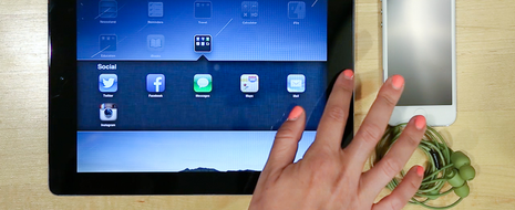 A tablet with a hand hovering over the home button has an array of icons displayed on the screen